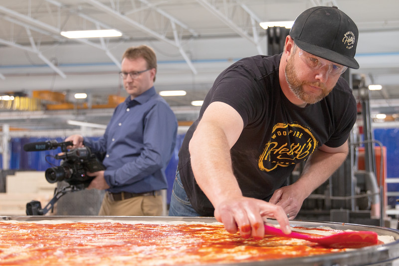 Matthew Gaston   The Sheridan Press<br>Travis Hetland, owner of Hetty's Woodfire Pizza, spreads pizza sauce evenly over a 6-foot diameter pizza Friday, March 22, 2019. Hetty's was invited to bake this massive pizza at EMIT, as a way of breaking in the company's new powder coat oven.