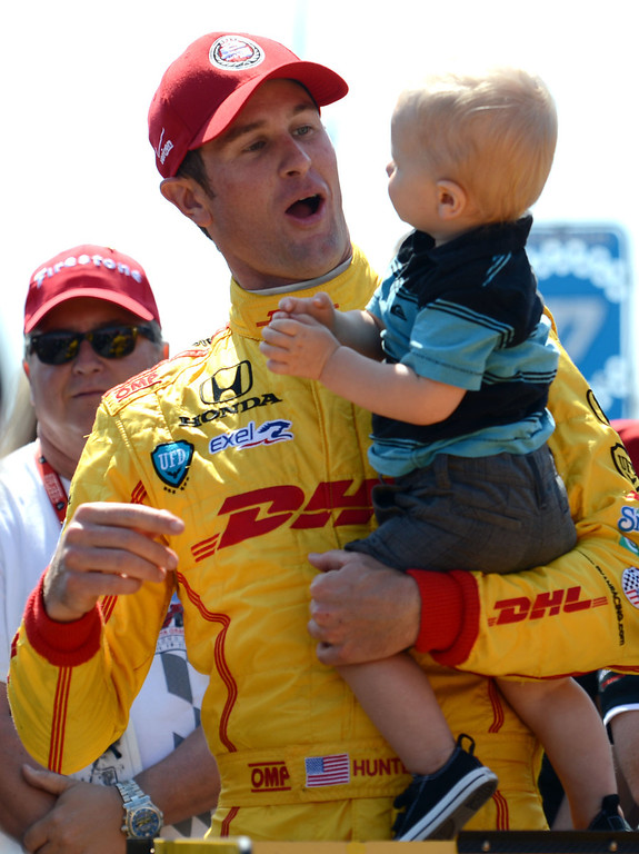 . IndyCar driver Ryan Hunter -Reay with his son Ryden, inside the pits,  after winning the IndyCar Qualifying & Firestone Fast 6 Saturday, at the 40th Annual Toyota Grand Prix of Long Beach.       Long Beach Calif., Saturday, April 12,  2014.   (Photo by Stephen Carr / Daily Breeze)