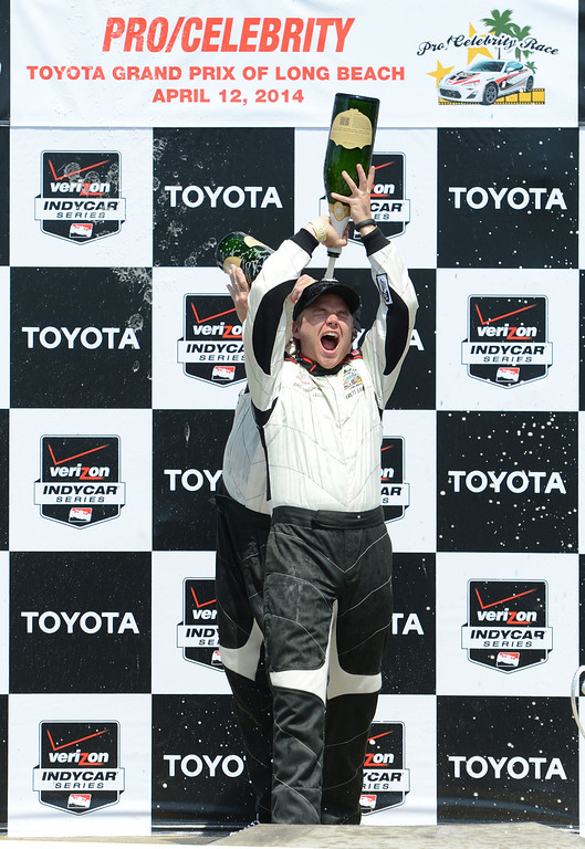 . Actor Brett Davern, dumps champagne on his head as pro driver Al Unser Jr. dumped it down his back after the two won the Toyota Pro / Celebrity Race Saturday, at the 40th Annual Toyota Grand Prix of Long Beach.   	    Long Beach Calif., Saturday, April 12,  2014.   (Photo by Stephen Carr / Daily Breeze)