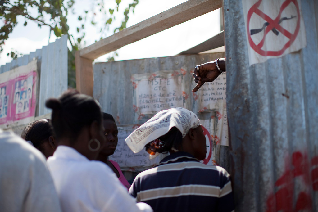 People are kept out of a cholera treatment center in downtown Port au Prince, Haiti. Visiting hours can be strict due to the high risk of spreading the disease, which has already claimed over 4,000 lives in Haiti since the outbreak.