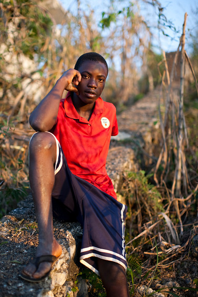 A young man takes a break from working the local farm land in the hills above Petionville, Port au Prince, Haiti.