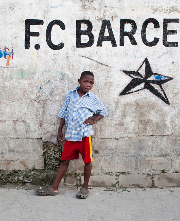 A young boy from the Delmas region of Port au Prince, Haiti poses in front of graffiti featuring the popular Spanish soccer club, F.C. Barcelona. Children often play soccer in alley ways with often with no shoes and flat balls.