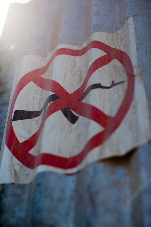 A sign showing a gun-free zone is seen on a gate to a cholera treatment center in downtown Port au Prince, Haiti. There is a growing black market for weapons in Haiti which has led to escalated levels of violence in the streets.