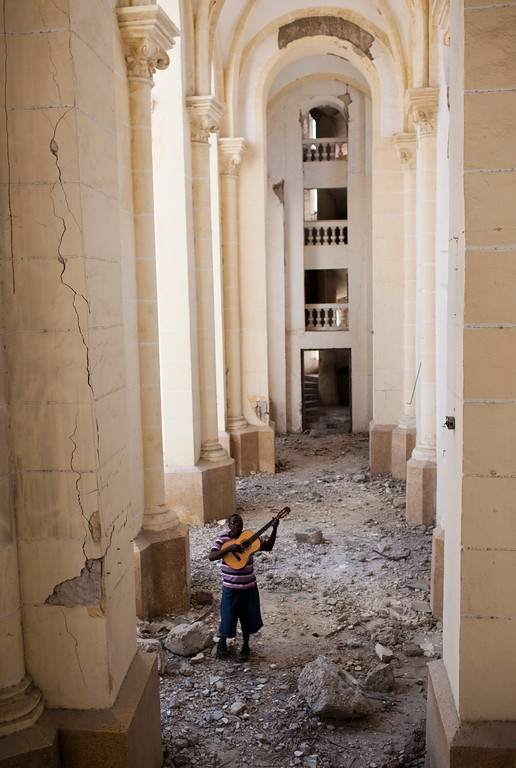 A man plays guitar in the ruins of the Cathedral of Our Lady of the Assumption, in downtown Port au Prince, Haiti. No restruction efforts have gotten underway after a year since the earthquake that destroyed it.