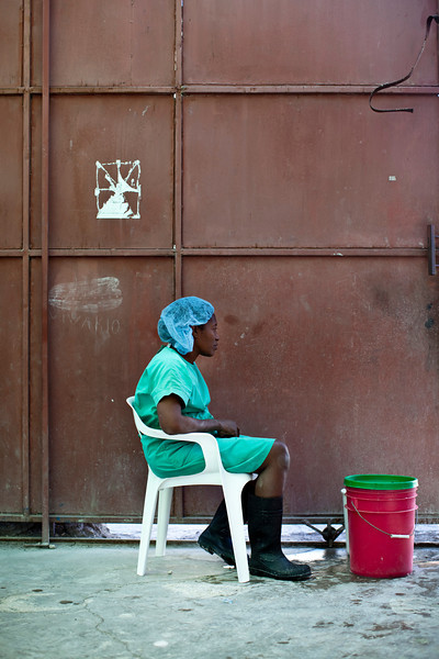 A woman stands at the entrance to a cholera treatment center waiting to rinse visitors' hands and feet in chlorine solution at the Kay Nou Health Center in downtown Port au Prince, Haiti.