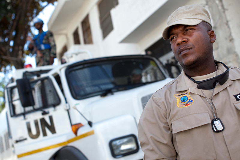 A Haitian National Police officer stands guard in front of a UN patrol near the KEP, the Haitian ministry of elections, in Port au Prince, Haiti.