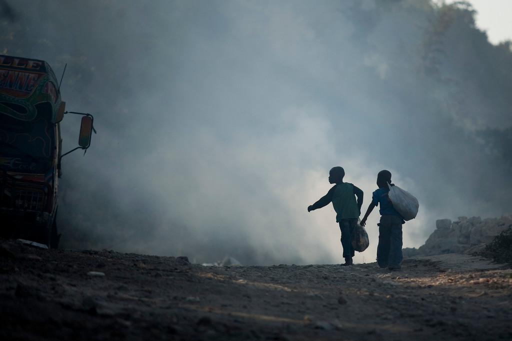 Children living in the hills above the Petionville region of Port au Prince, Haiti leave their school and walk past a trash fire. With no sanitation deptartment, garbage is often burned causing health problems of its own.