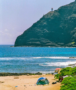 North Shore Beach with lighthouse on high cliff.