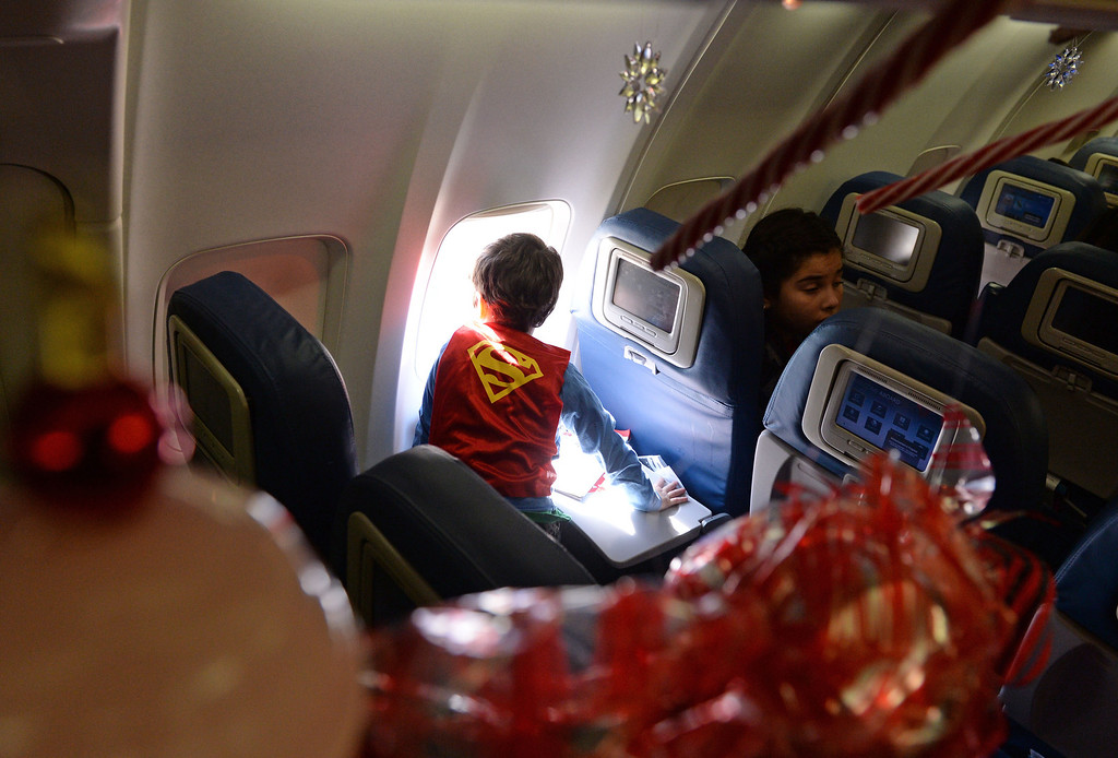 . Theo Apfelberg, looks out for Santa as the plane taxis around the airfield. Plane was decorated with holiday trimmings. Holiday in the Hangar at Delta Airlines at LAX. About 100 children from Children\'s Hospital, LA got to ride on a plane to the North Pole where holiday games and fun plus Santa awaited. (Dec 11, 2013. Photo by Brad Graverson/The Daily Breeze)