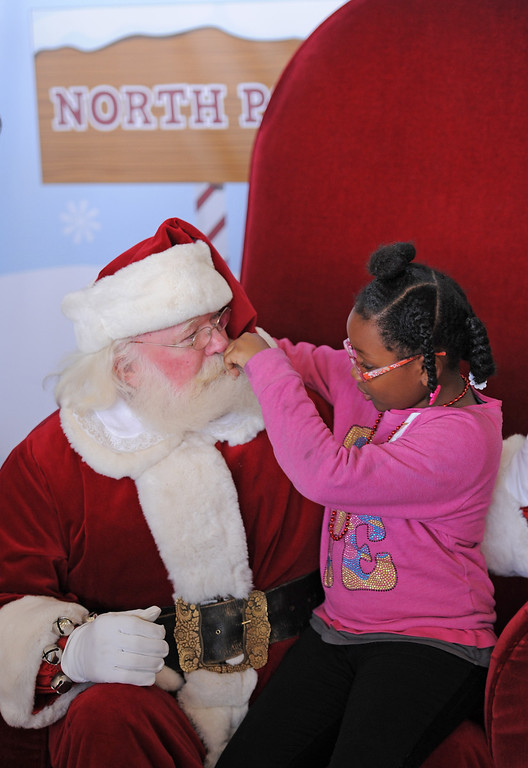 . Mariah Ruby-Simone Perkins had to look and see if Santa\'s beard was real or not. It was. Holiday in the Hangar at Delta Airlines at LAX. About 100 children from Children\'s Hospital, LA got to ride on a plane to the North Pole where holiday games and fun plus Santa awaited. (Dec 11, 2013. Photo by Brad Graverson/The Daily Breeze)