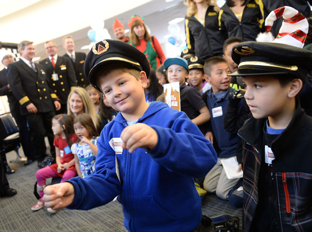 . Julian Allen Davis wears a captains hat and pretends to fly a plane at the Holiday in the Hangar at Delta Airlines at LAX. About 100 children from Children\'s Hospital, LA got to ride on a plane to the North Pole where holiday games and fun plus Santa awaited. (Dec 11, 2013. Photo by Brad Graverson/The Daily Breeze)