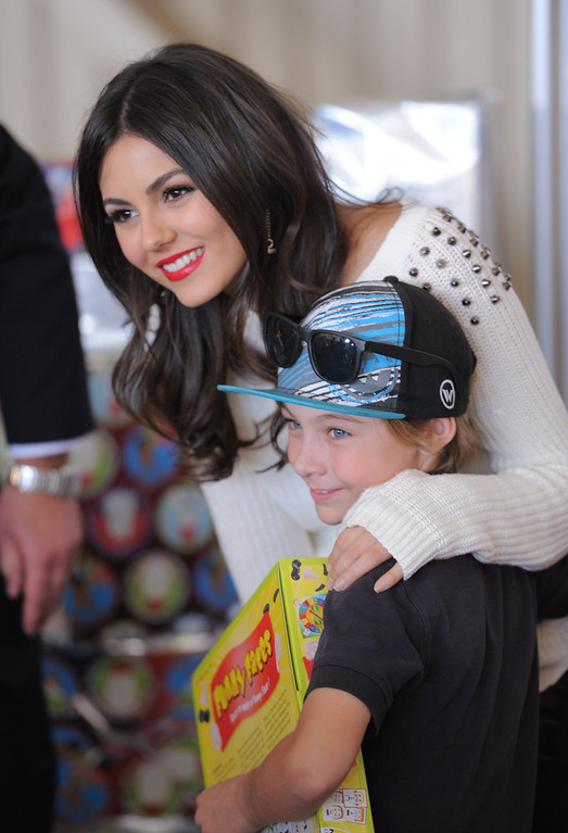 . Actress Victoria Justice poses with kids. Holiday in the Hangar at Delta Airlines at LAX. About 100 children from Children\'s Hospital, LA got to ride on a plane to the North Pole where holiday games and fun plus Santa awaited. (Dec 11, 2013. Photo by Brad Graverson/The Daily Breeze)