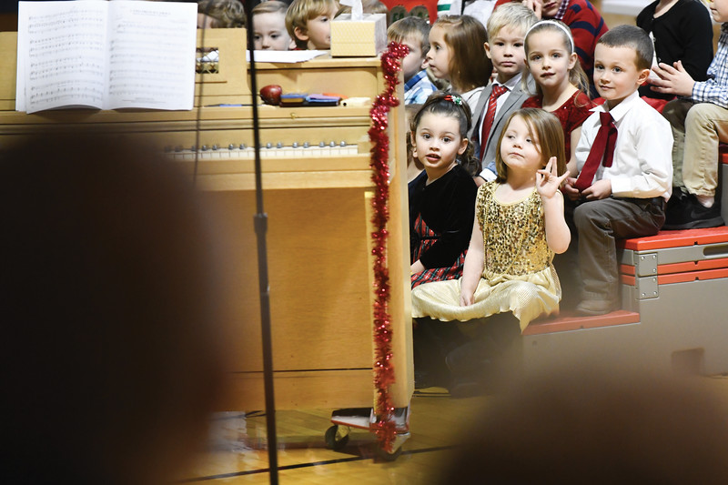 Matthew Gaston | The Sheridan Press<br>Holy Name Catholic School pre-K student Olivia Dyer waves to her family before performing in the Christmas program Thursday, Dec. 20, 2018.