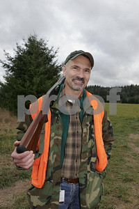 A pheasant hunter pauses with his shotgun to talk to friends.
