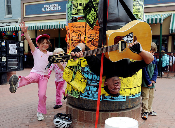 """Charlie Cartier was discovered playing guitar hanging upside down on a kiosk on the Pearl Street Mall on Sunday. Fiona Nugent, left, was one of the children inspired to run around Charlie.<br /> For video of his concert, go to  <a href=""""http://www.dailycamera.com"""">http://www.dailycamera.com</a><br /> Cliff Grassmick / May 9, 2010"""