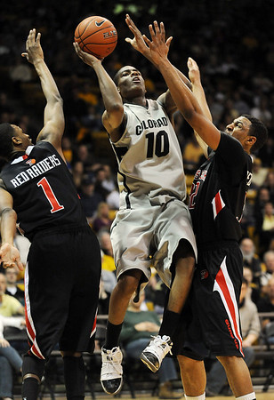 "Alec Burks of CU goes up between Brad Reese, left, and Mike Singletary, both of Texas Tech.<br /> For more basketball photos, go to photo galleries at  <a href=""http://www.dailycamera.com"">http://www.dailycamera.com</a>.<br /> Cliff Grassmick / March 6, 2010"