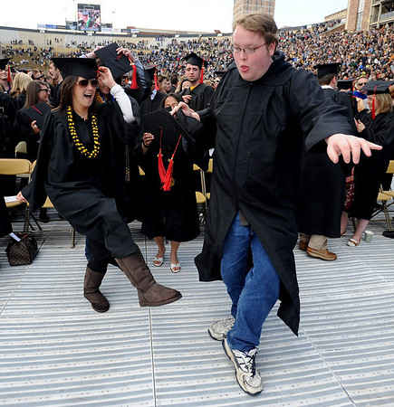 """Kelly Schuberth, left, and  Adam Ladwig, both Journalism graduates, dance to the song """"In the Mood,"""" after the ceremony.<br /> The University of Colorado conferred 5,825 degrees at Folsom Field Friday, May 7, 2010.<br /> Cliff Grassmick / May 7, 2010"""