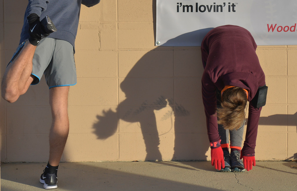 Justin Sheely | The Sheridan Press<br /> Runners stretch against a wall during the Sheridan Recreation District's second-annual Resolution Run 5k at Thorne-Rider Park Saturday, Jan. 6, 2018.