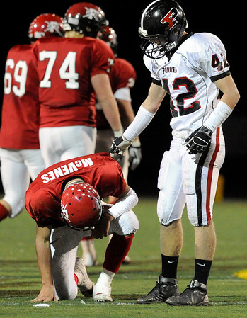 """Pomona junior Keegan Pratt, right, tries to console Fairview quarterback Michael McVenes after he fumbled the ball in the second quarter of the football game on Friday, Oct. 15, at Recht Field in Boulder. Pomona recovered the fumble. Pomona defeated Fairview 21-3.<br /> For photo gallery go to  <a href=""""http://www.dailycamera.com"""">http://www.dailycamera.com</a><br /> Jeremy Papasso/ Camera"""