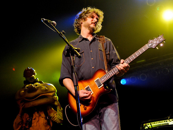 """Leftover Salmon band member Drew Emmitt plays his guitar as The Mayor McCheese dances in the background dressed as a firefighter while performing on Saturday, Oct. 9, during the Fourmile Fire benefit concert at the 1st Bank Center in Broomfield.<br /> For video go to  <a href=""""http://www.dailycamera.com"""">http://www.dailycamera.com</a><br /> Photo by Jeremy Papasso/ Camera"""