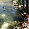 Matt Lafontaine, 23, of Boulder, at left, backflips off a rope-swing into the Boulder Creek on Saturday, July 24, 2010, while other river enthusiasts watch and enjoy the warm weather.<br /> Jeremy Papasso/ Camera