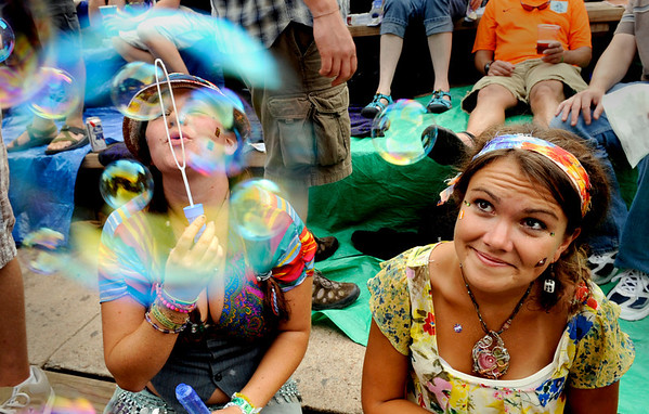 Megan Segall, from Miami, blows soap bubbles from her seat while Emily Hennelly, of Knoxville, Tenn., watches at the String Cheese Incident concert at Red Rock Amphitheater in Morrison, Colorado July 23, 2010.  CAMERA/Jeremy Papasso