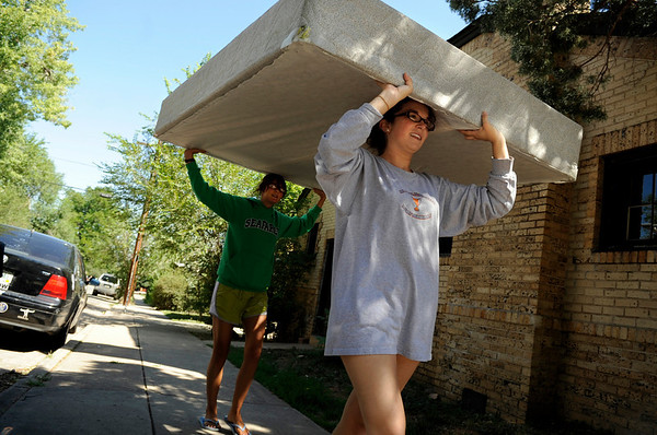University of Colorado junior Emma Polden, at right, gets some help  from sophomore Meredith Tousignant while moving a mattress into her new apartment on on Saturday, Aug. 14, in the university hills neighborhood in Boulder. The two had to carry the mattress five blocks to Polden's new residence.<br /> Jeremy Papasso/ Camera
