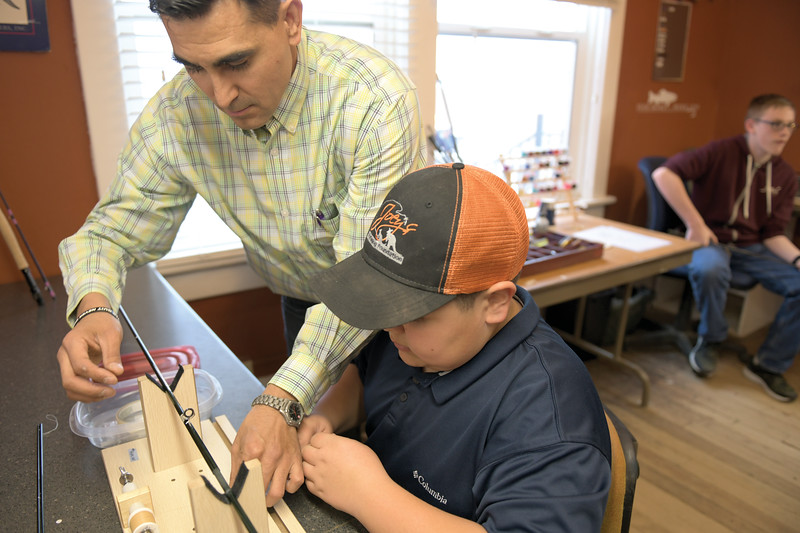 Matthew Gaston | The Sheridan Press<br>Joey Puettman, left, assists 12-year-old Anthony Kindle with setting up to thread an eyelet on to the rod Kindle is building at Joey's Fly Fishing Foundation Thursday, April 11, 2019.