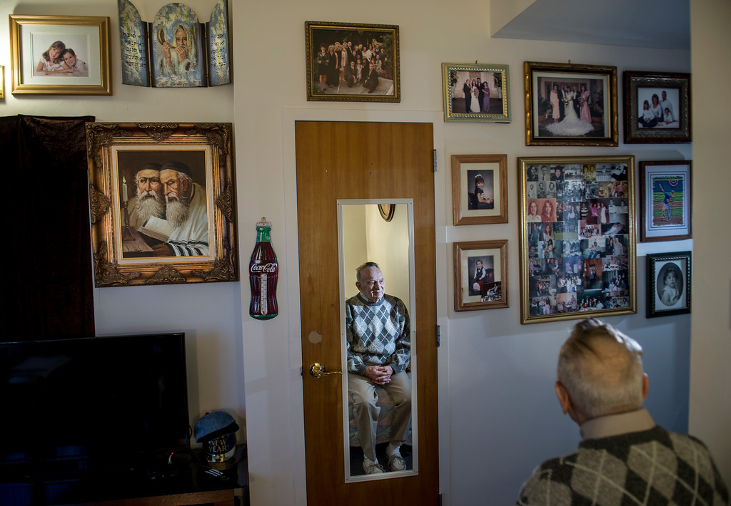 . Joseph Neustadt, 89, reflected, gazes at a wall adorned with pictures of his wife, son, daughter and his four grandchildren in his room at the Los Angeles Jewish Home for the Aging-Eisenberg Village in Reseda on Wednesday, January 25, 2017. Joseph Neustadt who was born and raised in Riga Latvia, Baltic states, was the lone survivor of the Holocaust from his immediate family. He says at the age of 14 he was placed in a concentration camp for 4 years, he lost his mother, father, two sisters and a brother during World War II. Photo by Ed Crisostomo, Los Angeles Daily News/SCNG)