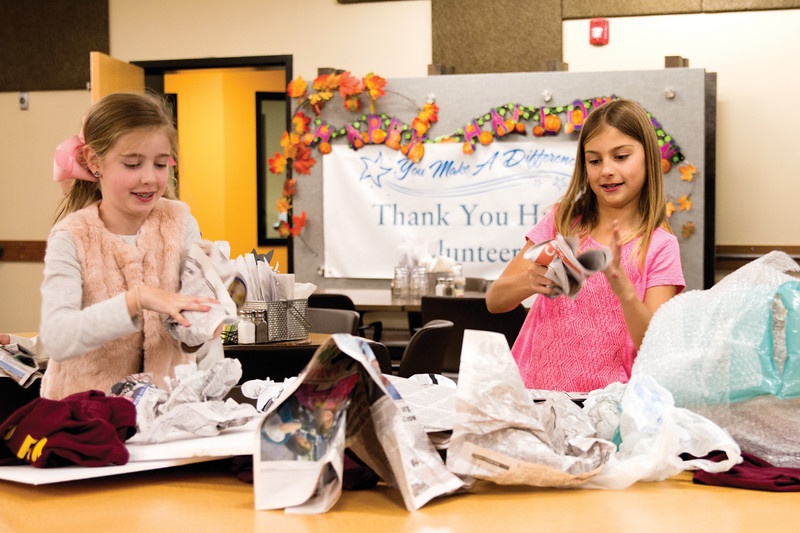 Matthew Gaston | The Sheridan Press<br>After thouroghly wrapping their pumpkin in bubble wrap, Alexis Evans, right and Allyson Bauer, left, both 9 years old; wad up newspaper for extra cushioning for the first phase of the pumpkin drop contest Friday, Oct. 19, 2018.