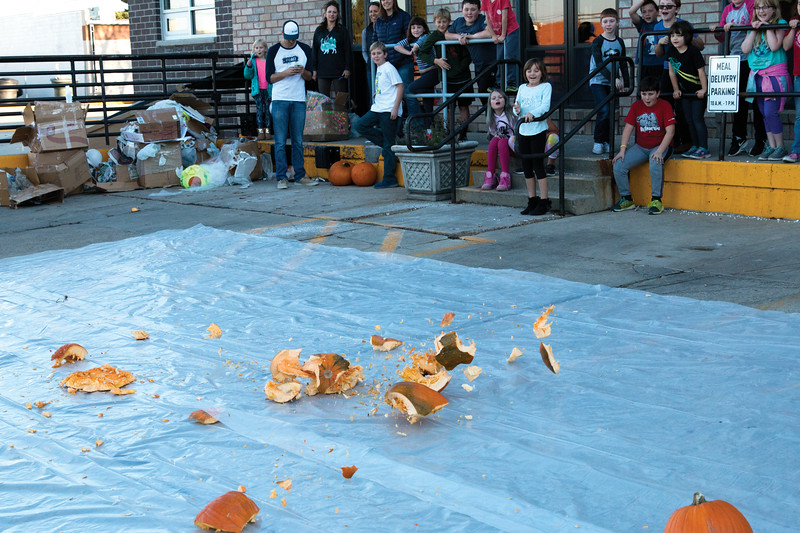 Matthew Gaston | The Sheridan Press<br>A pumpkin explodes as it hits the ground to the delight of the childern gathered at The Hub for the Kids Life/Impact pumpkin drop Friday, Oct. 19, 2018.