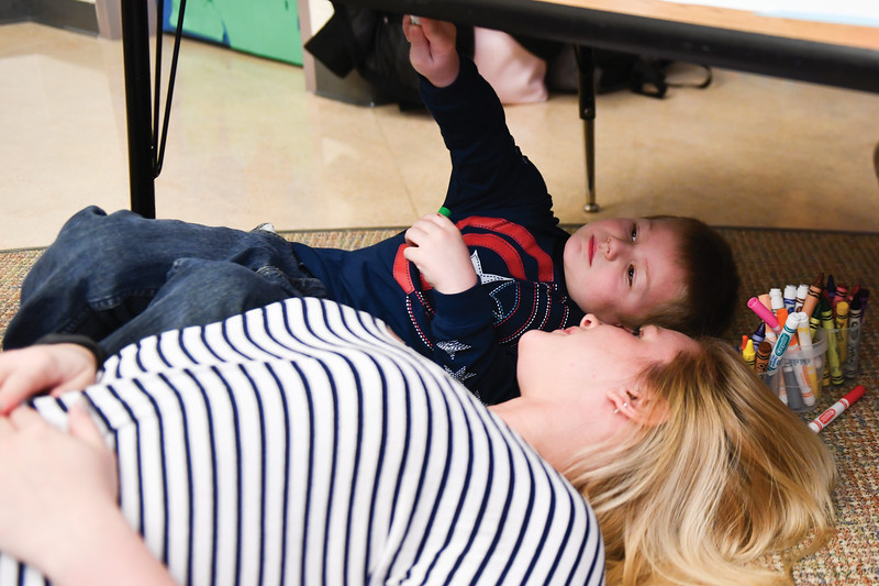 Matthew Gaston | The Sheridan Press<br>Braylynn Dannels lies on the floor with her son 3-year-old son, Liam, as he creates a work of art on a piece of paper taped to the bottom of a desk during the Kindlers program Wednesday, Jan. 9, 2019.