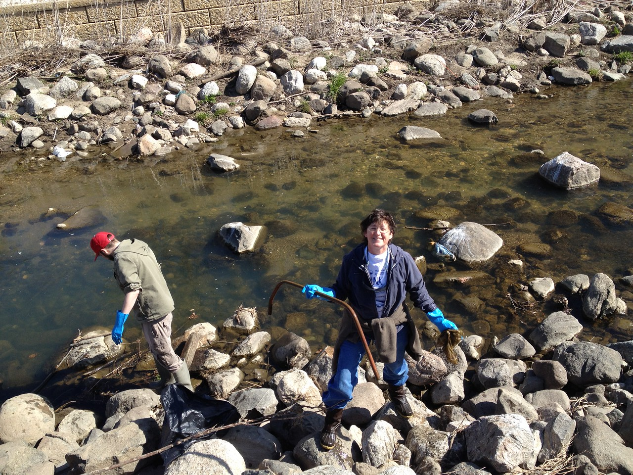 Kelly O'Ferrell, CFL Hasler Lab Center Assistant, digs out a bar from the river.
