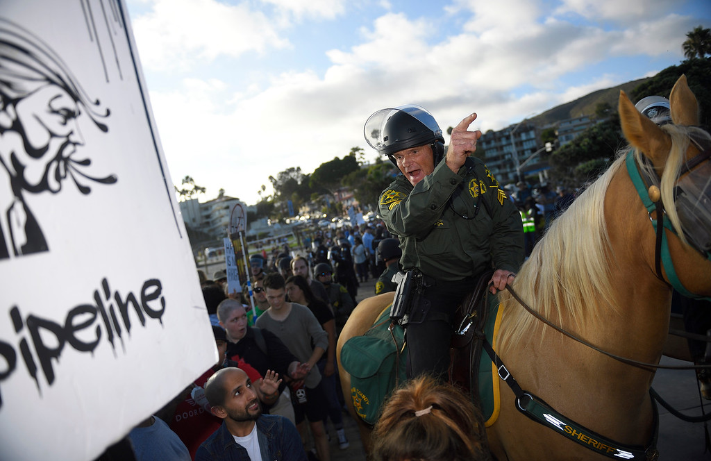 . Deputy Sgt. Frazee from the Orange County Sheriff Mounted Unit works to keep protesters from oposing sides from clashing during the protest in Laguna Beach. Kevin Sullivan, Orange County Register/SCNG