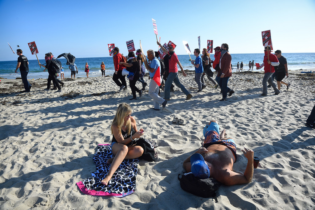 . Counter protesters walk by beachgoers during an illegal immigration rally at Laguna Beach. Kevin Sullivan, Orange County Register/SCNG