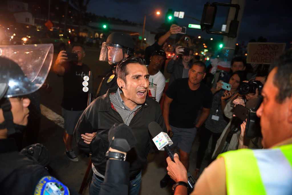 . A protester talks to the media as he\'s arrested during a demonstration on Main Beach in Laguna Beach Sunday August 20, 2017. (Kevin Sullivan, Orange County Register/SCNG