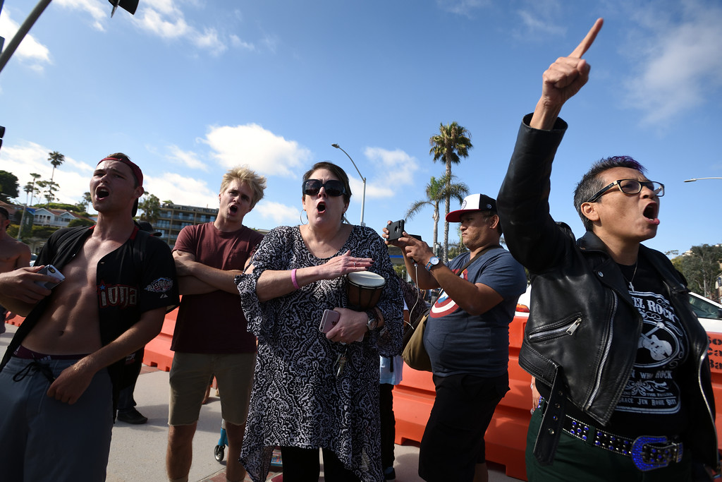. Cynthia Thompson, center, and Lola Ramirez of Laguna Beach, right, join other during a demonstration at Pacific Coast Highway near Broadway St. in Laguna Beach. Mindy Schauer, Orange County Register/SCNG