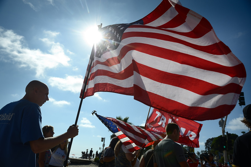 . Tyler Devin, 22, of Los Angeles holds up an American flag during during a protest in Laguna Beach. Devin said he wasn�t there representing anyone. Kevin Sullivan, Orange County Register/SCNG