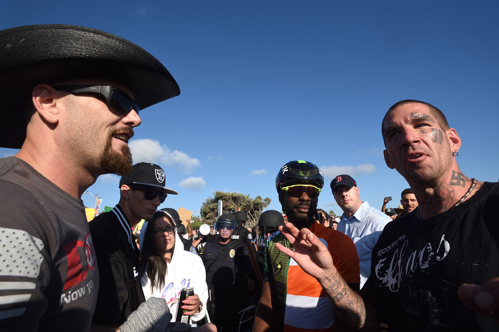 . A protest organizer, left, complains to Tommy Valentina, right, for showing up with a swastika on his neck. Valentina agreed to put his shirt on saying that he was not a Nazi, �I�m just me.� Mindy Schauer, Orange County Register/SCNG