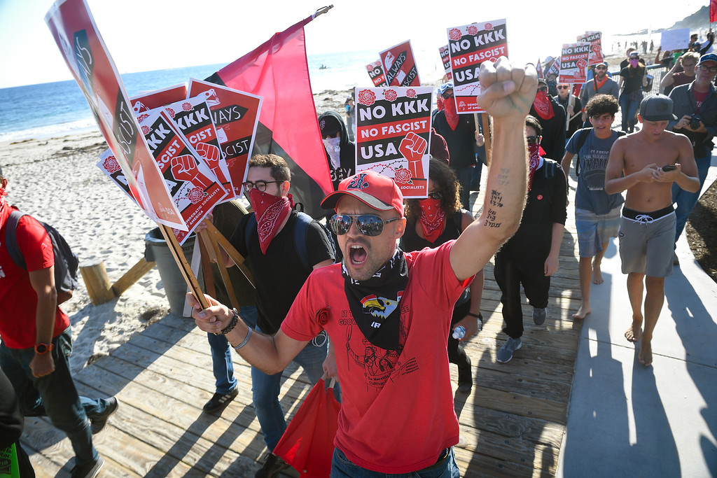 . John Motter, 29, of Los Angeles, walks with anti KKK protesters as they march down the boardwalk during an illegal immigration rally at Laguna Beach. Kevin Sullivan, Orange County Register/SCNG
