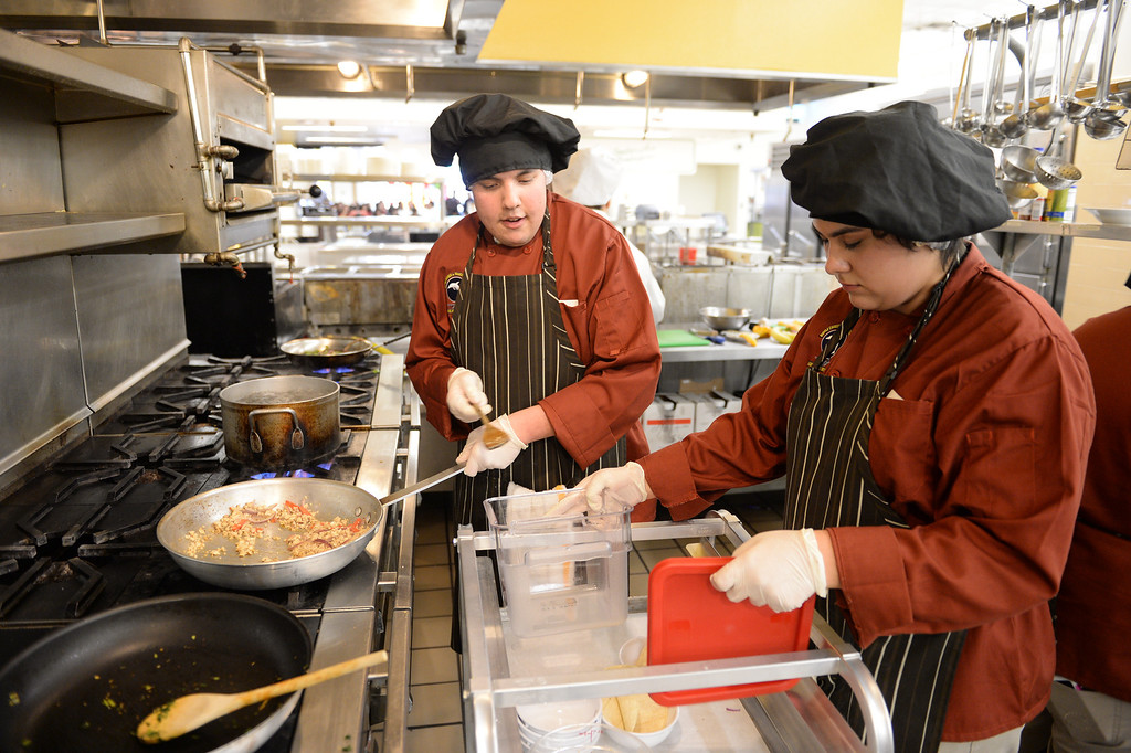 """. LAUSD \""""Cooking Up Change\"""" culinary competition for high school students held at LA TradeTechnical College. Doyle CTC chefs Esteban Tostado, left, and Leticia Sanchez cook Jam-exican jerk chicken. (Thurs. Jan 30, 2014 Photo by Brad Graverson/The Daily Breeze)"""