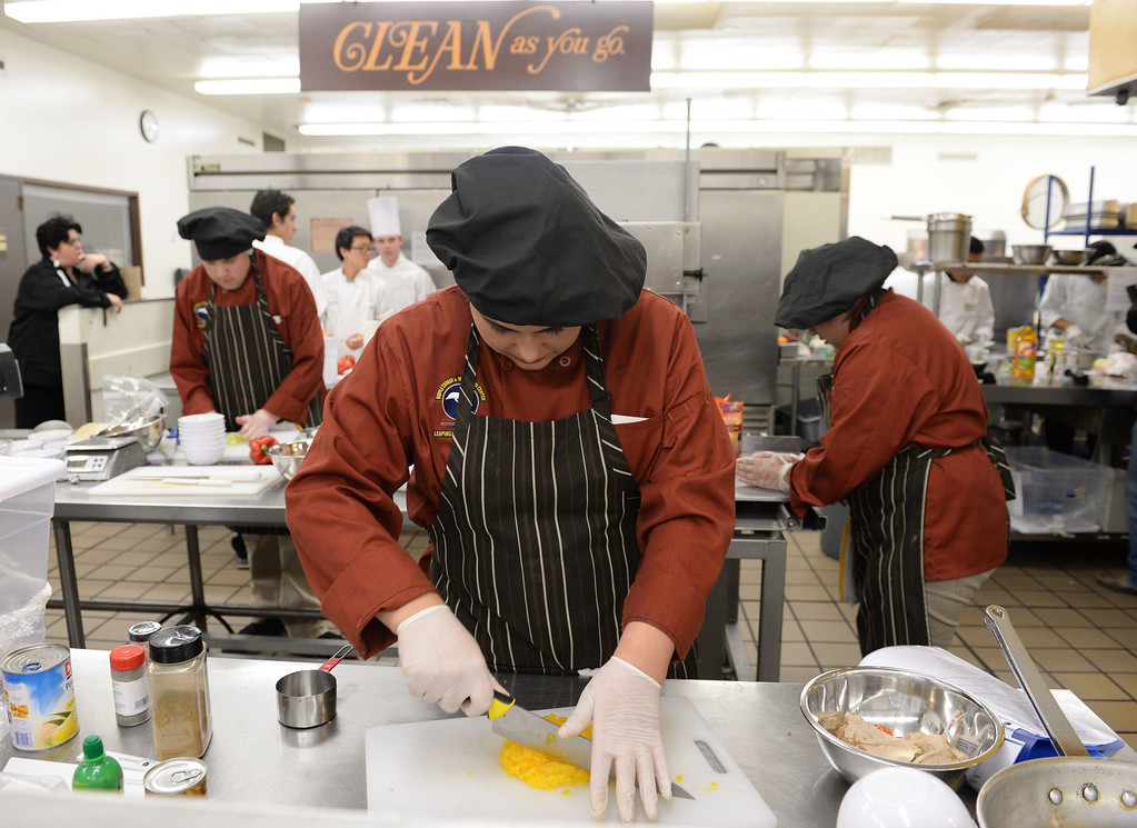 """. LAUSD \""""Cooking Up Change\"""" culinary competition for high school students held at LA TradeTechnical College. Doyle CTC chef Leticia Sanchez chops mango for a salsa.  (Thurs. Jan 30, 2014 Photo by Brad Graverson/The Daily Breeze)"""