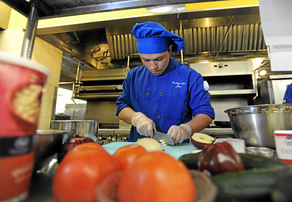 . Jose Garcia, a Senior at Francis Polytechnic High School in Sun Valley, chops up some apples for his recipe during a competition at LA Trade Technical College. Students hope to be chosen to participate in the National Competition in Washington this June.  Los Angeles , CA. January 30, 2014 (Photo by John McCoy / Los Angeles Daily News)