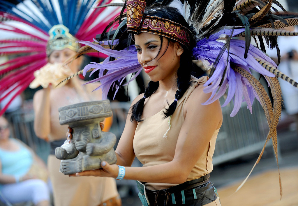 . Aida Landeros,left, and Nashua Mena offer an Aztec blessing to kick off the 5th Annual Latin American Festival on North Pine in Long Beach, CA. on September 7, 2013.(Photo by Sean Hiller/Press Telegram)