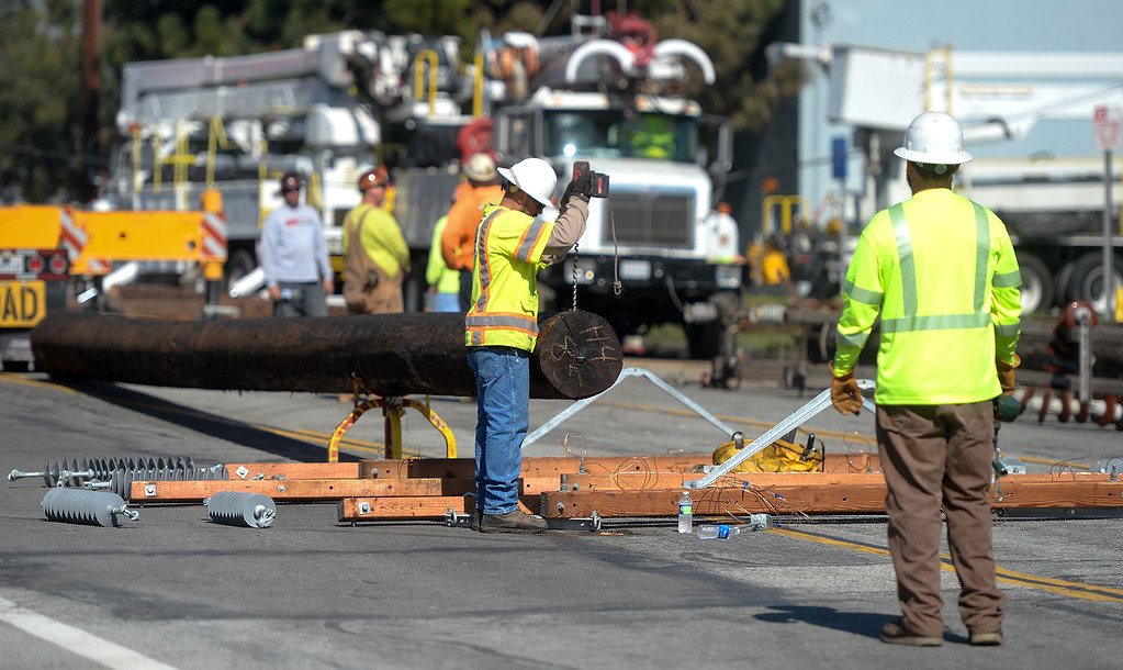 . Edison workers build a new power pole after a truck ran into a power pole causing a five-alarm fire at a plastic recycling plant on the 12200-block of Los Nietos Rd. in Santa Fe Springs, Calif. on Tuesday March 14, 2017. The fire started after a truck crashed into a power pole which caused a tree to catch fire that spread to the recycling plant. (Photo by Keith Durflinger/Whittier Daily News/SCNG)