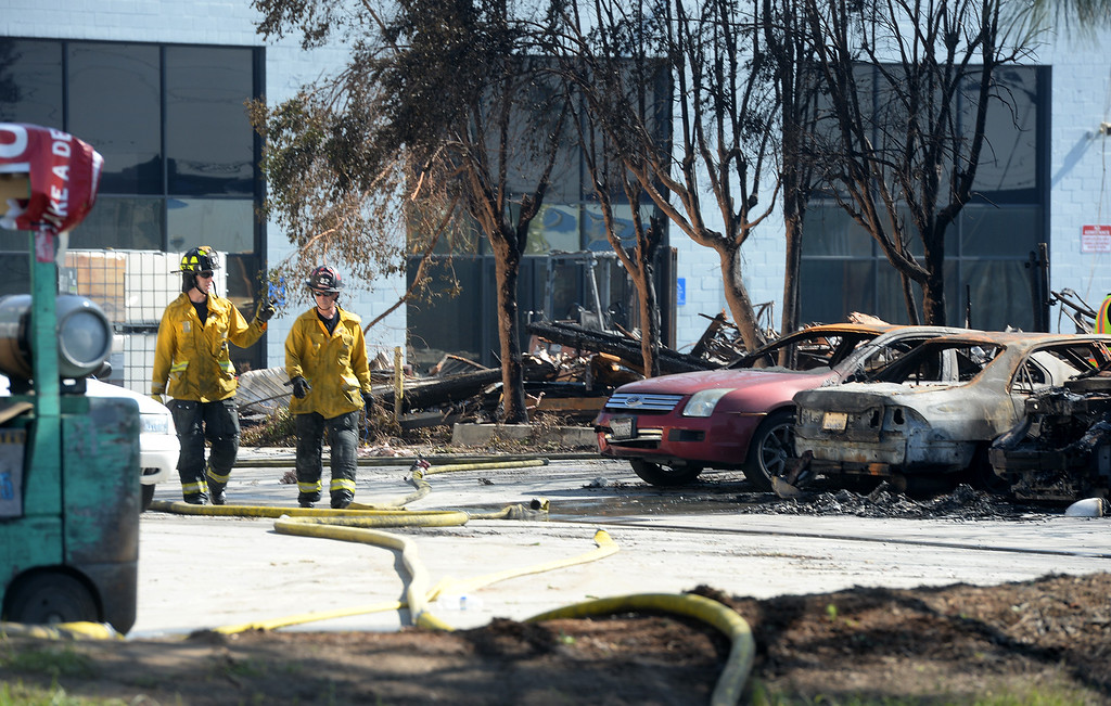. Santa Fe Springs firefighters conduct mop up after a five-alarm fire at a plastic recycling plant on the 12200-block of Los Nietos Rd. in Santa Fe Springs, Calif. on Tuesday March 14, 2017. The fire started after a truck crashed into a power pole which caused a tree to catch fire that spread to the recycling plant. (Photo by Keith Durflinger/Whittier Daily News/SCNG)