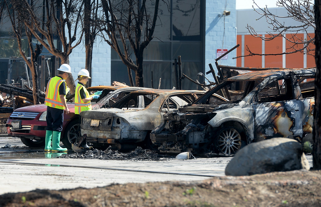 . Santa Fe Springs health and safety inspectors look over burned cars from the fire at a plastic recycling plant on the 12200-block of Los Nietos Rd. in Santa Fe Springs, Calif. on Tuesday March 14, 2017. The fire started after a truck crashed into a power pole which caused a tree to catch fire that spread to the recycling plant. (Photo by Keith Durflinger/Whittier Daily News/SCNG)