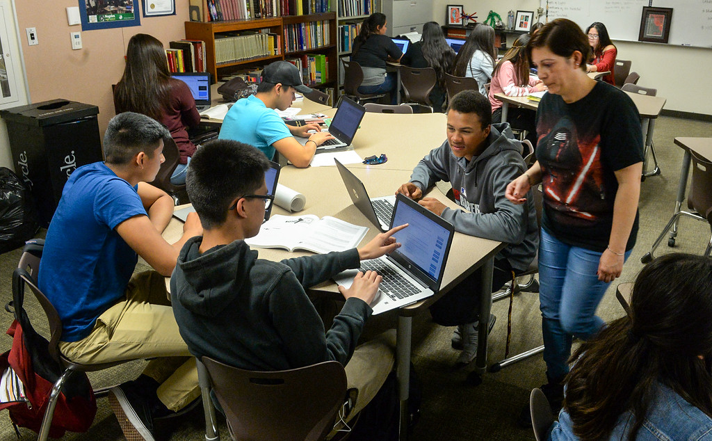 . Teacher Martha Solano, right, helps students, Matthew Alvarez, left, Jordan Gaitan, center and Bryce Wills, right center, in their AP English class at Nogales High School in La Puente on Wednesday April 12, 2017. Rowland Unified had one of the highest increases in graduation rate in the area. (Photo by Keith Durflinger/Whittier Daily News/SCNG)