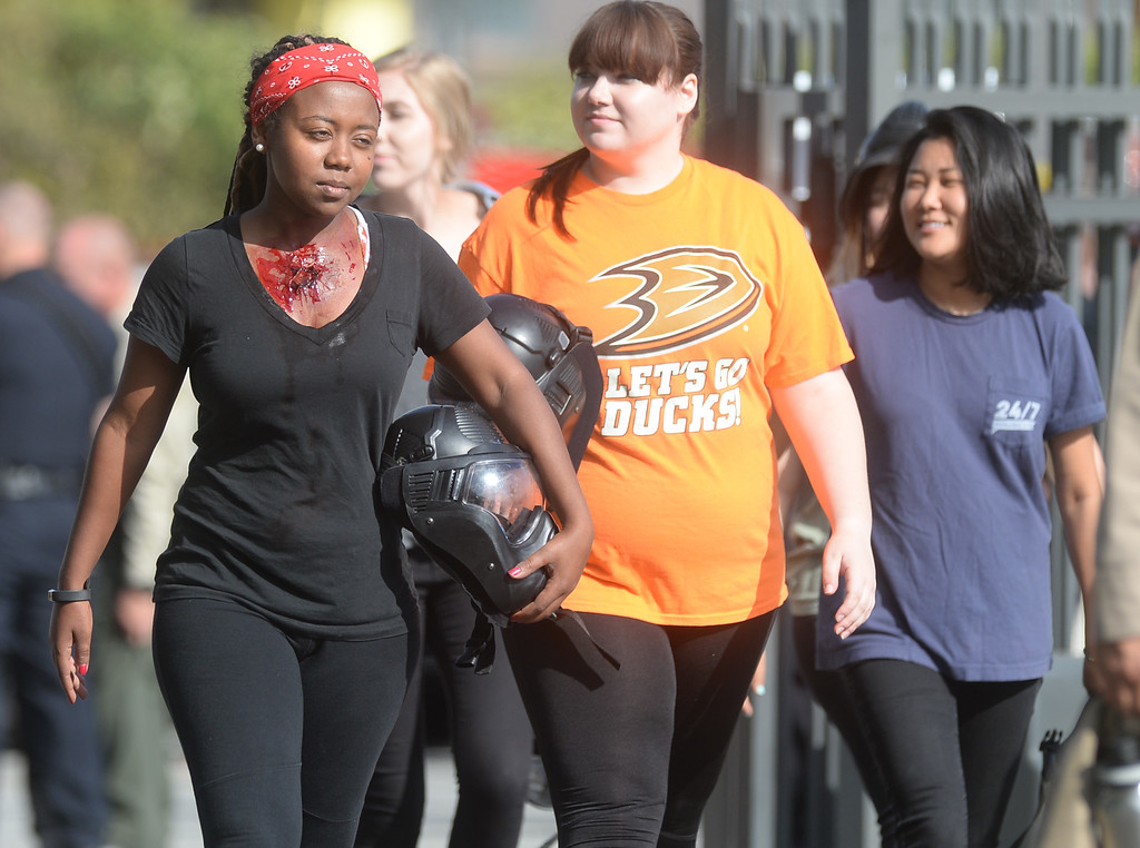 . Student Mekdes Ekey, left, walks in with a simulated gunshot wound during an active shooter response drill at Biola University in La Mirada on Wednesday April 19, 2017. The training incorporated simulated gunfire, simulated injuries and role players in the university. (Photo by Keith Durflinger/Whittier Daily News/SCNG)