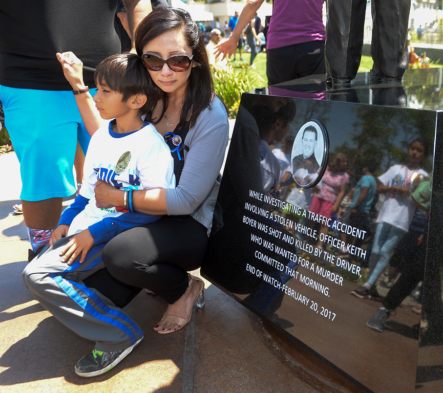 . Leticia Del Villar, girlfriend of the late Officer Keith Boyer, holds her son, Aden, as she looks at the plaque  that is added to the Whittier Police Memorial during the Open House on Penn Street in Whittier on Saturday May 13, 2017. (Photo by Keith Durflinger/Whittier Daily News/SCNG)